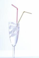 flute com agua gelo e duas palhinhas sobre fundo branco