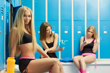 Sexy girls resting in dressing room after workout