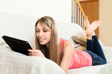 Happy girl laying on couch with tablet