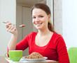 woman in red eats buckwheat porridge
