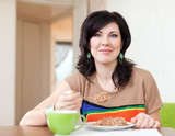 Pretty woman eats  cereal at home