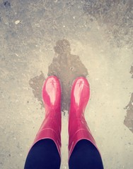 legs in pink rubber boots at puddle