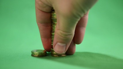 hand puts a stacks of coins on a green background