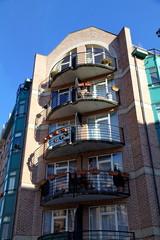 Façade d'immeuble avec balcons à l'ombre et au soleil