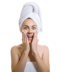Surprised woman wrapped in a towel applaying cream or moisturize
