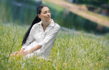 Adorable female with closed eyes relaxing on meadow