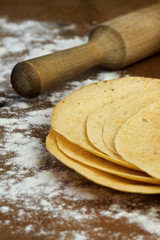 stack of tortillas on a wooden background