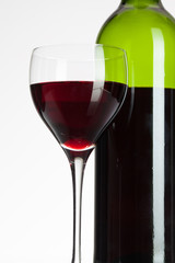 Wine glass and bottle with red wine