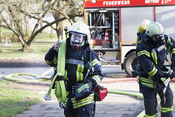 Feuerwehrmann trägt Schlauch