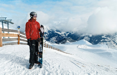 Male snowboarder against winter mountains background