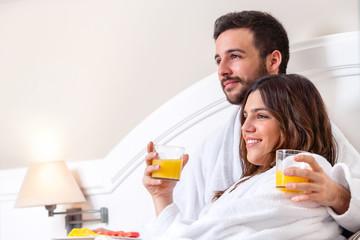 Couple in bathrobe drinking orange juice.
