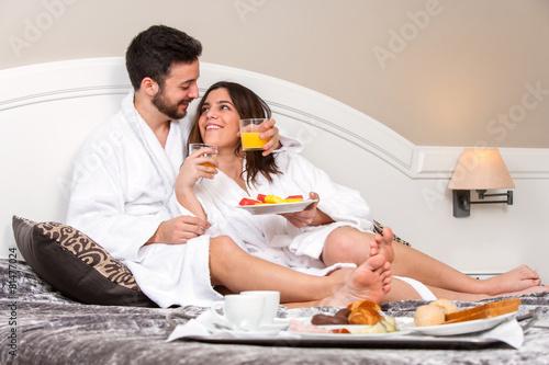 Leinwanddruck Bild Young couple on honeymoon in hotel room.