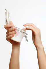 flexible and beautiful female hands holding jar of cream