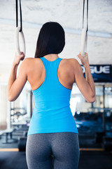 Rear view portrait of woman working out on gimnastic rings