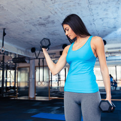 Cute woman working out with dumbbells