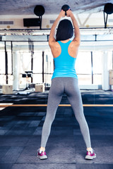 Back view portrait of a woman working out with weight
