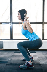 Young woman doing squats with barbell