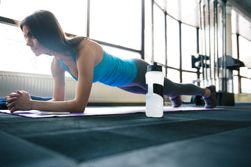 Young fit woman working out on yoga mat