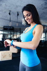 Smiling young woman using activity tracker