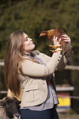 Young woman playing with chicken