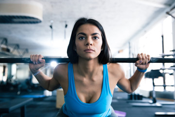 Attractive young woman working out with barbell