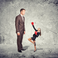 Large businessman looking at small businesswoman in boxing