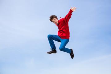 Teenage boy running, jumping outdoor