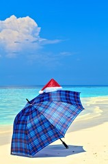 Blue Umbrella Is On A Beach With Santa Hat