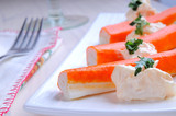 Surimi sticks with sauce on a white plate