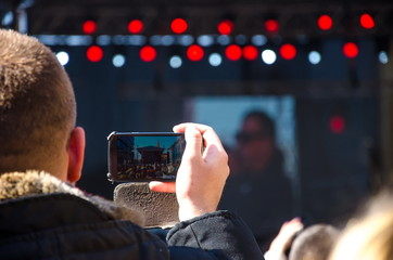 Man shooting a music festival with your mobile phone