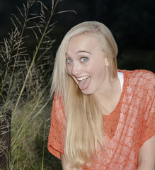 Beautiful young girl outdoors in field making funny faces