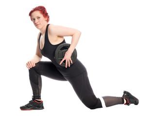 Junge Frau trainiert mit einer Hantelscheibe