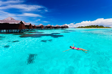 Young woman swimming from hut in tropical lagoon