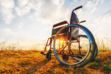 Empty wheelchair on the meadow. Miracle concept