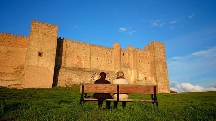 Abuelas sentadas en banco frente a castillo