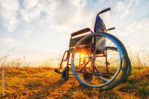 Empty wheelchair on the meadow. Miracle concept - 81482204