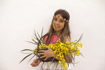 Niña con diadema de rosas y cesta con flores amarillas