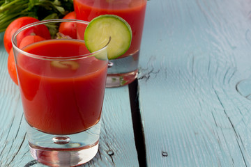Tomato gazpacho in glasses over blue wooden table