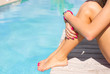 Woman sitting on the deck by the swimming pool - 81484480