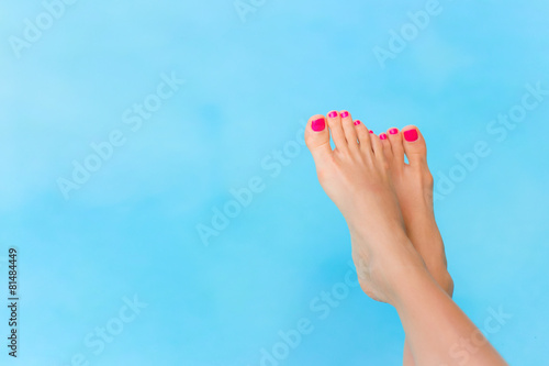 Bare woman feet over blue swimming pool water - 81484449