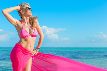 Happy woman in pink bikini covered with piece of fabric