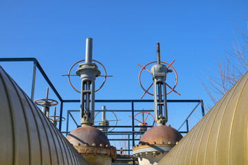 Gas pipes with valves on a background of blue sky