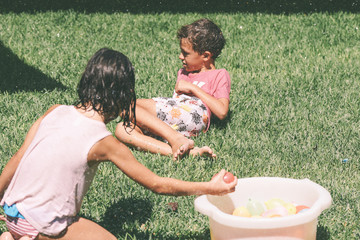 Happy children playing with water balloons