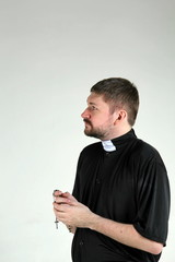 Catholic priest with rosary looking left