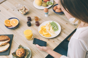Girl using mobile phone while having breakfast