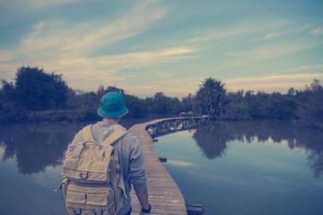 traveler walking over wooden bridge in park