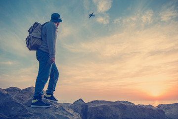 traveler near the sea looking far away at airplane