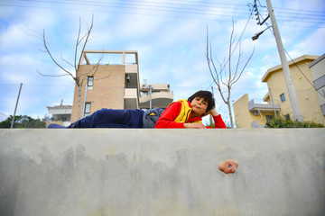 Child laying over a concrete wall