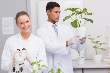 Scientist smiling at camera while colleague looking at plant