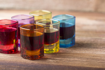 Filled coloured glasses on wooden background